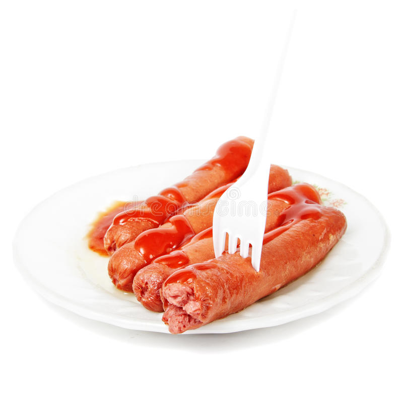 Sausages dressed with ketchup and fork stock photo