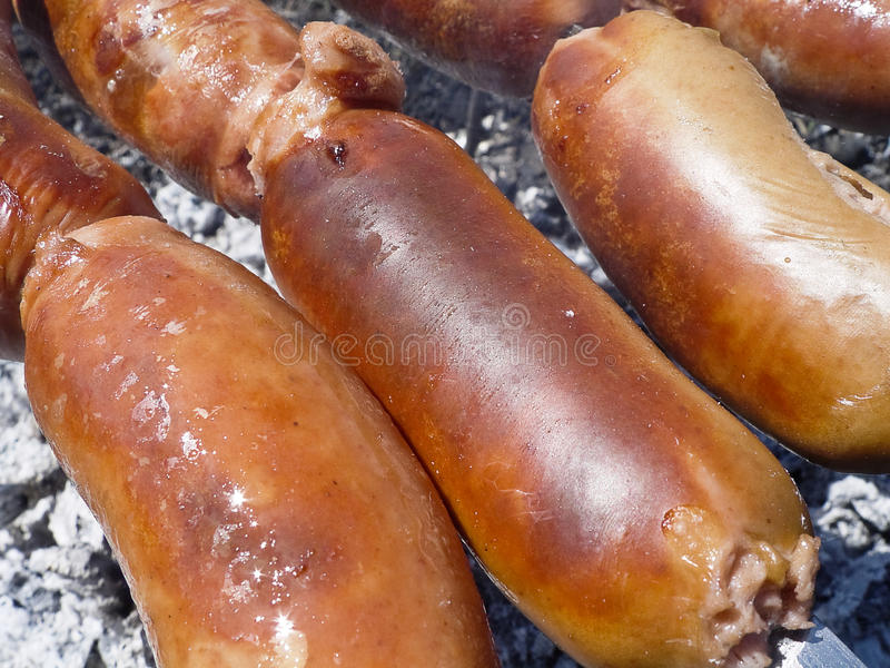 Sausages on fire. Delicious sausages, roasted on the fire stock image