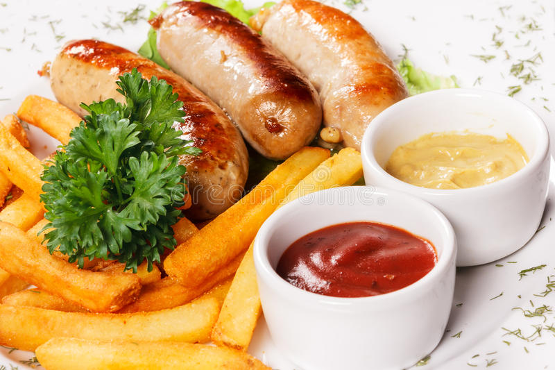 Sausages a grill with French fries and fennel royalty free stock photos