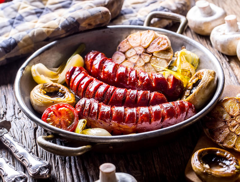 Sausages. Grill sausages. Grilled sausage with mushrooms garlic tomatoes and onions.  royalty free stock photos