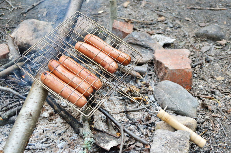 Sausages grilled over charcoal on the grate fire stock photography