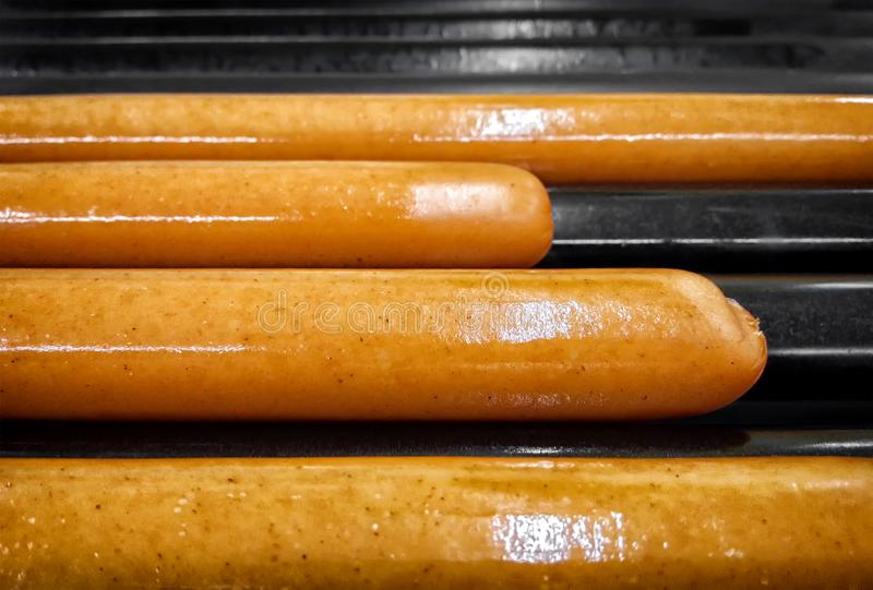Sausages for Hot Dogs on a Black Grill. royalty free stock images