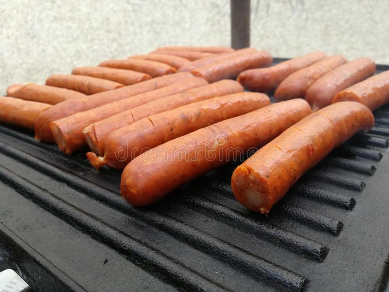 Sausages on hot plate. Red sausage on black hot plate, delicious backon meat and grill ideal food for summer. Beautiful smell in garden and abstract wallpaper or stock photography