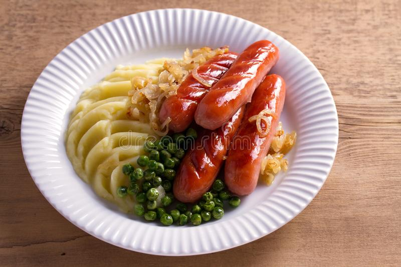Sausages, mashed potatoes, green peas and onion gravy. Homemade Bangers and Mash. royalty free stock images