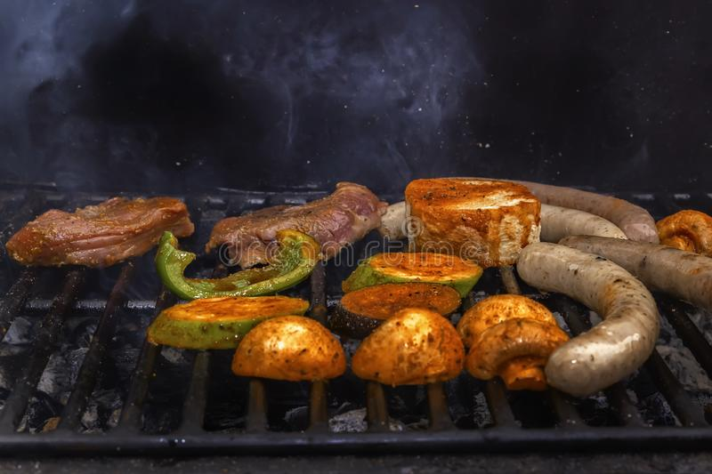 Sausages, meat steak, vegetables, mushrooms are cooked on a charcoal grill. Street food. Close-up stock photography