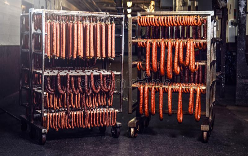 Sausages on racks in a storage room in meat processing factory. stock images