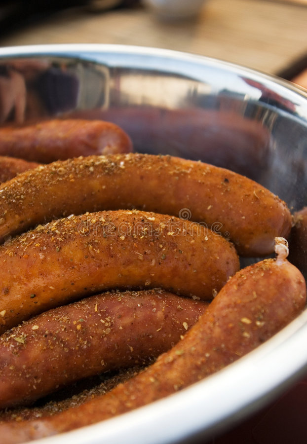 Sausages ready for barbecue. Some Polish sausages covered with spices, in a metal dish, waiting to be grilled on a barbecue stock photography