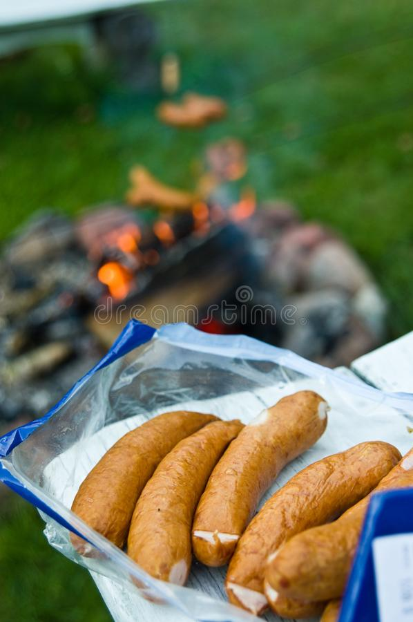 Sausages ready for a campfire barbecue. Pack of fresh sausages ready for a campfire barbecue as seen in bokeh background. Camping abstract royalty free stock image