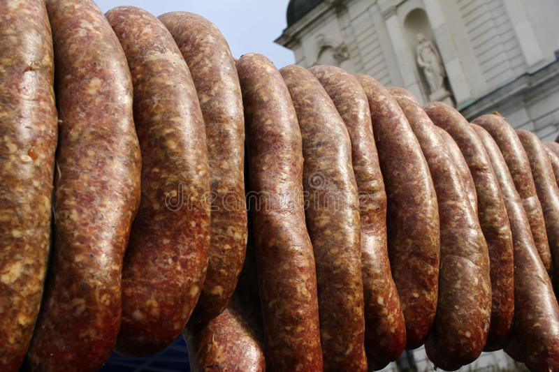 Sausages. Sausages hang outdoor for sale on a street market.Home made meat salami sausage at street market hanging in line under s royalty free stock photo