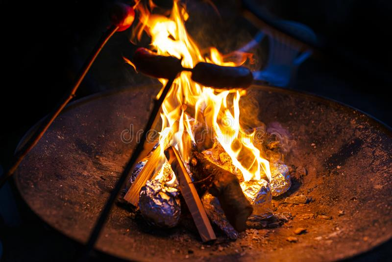 Sausages on a stick roasted over a bonfire in the evening. stock image
