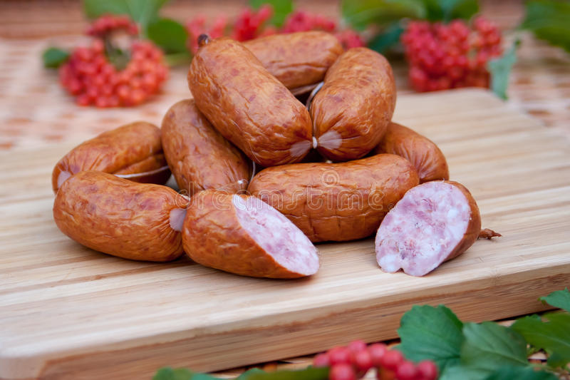 Sausages on a wooden board. Raw sausages on a wooden chopping board stock image