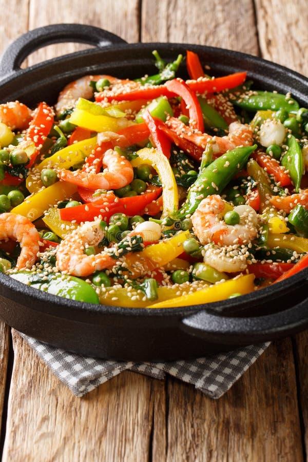 Sauté asiatique délicieux de la crevette avec des légumes, plan rapproché de sésame dans une poêle vertical photos libres de droits