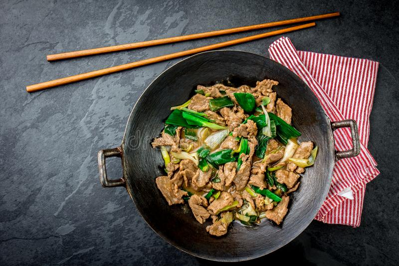 Sauté mongol de boeuf de chinois traditionnel dans le wok chinois de fonte avec faire cuire des baguettes, fond en pierre d'ardoi image stock