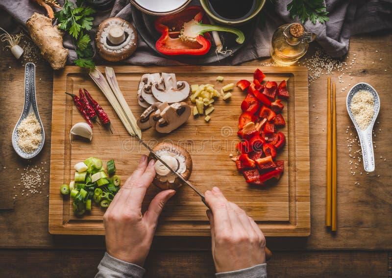 Sauté végétarien faisant cuire la préparation Les femmes les mains que femelles coupent des légumes pour le sauté sur le fond de  image libre de droits