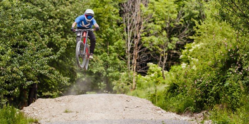 Saut de vélo de Mountainbiker en descendant image libre de droits