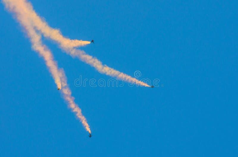 Saut des parachutistes quatre avec de la fumée et la mouche dans le ciel bleu photo libre de droits