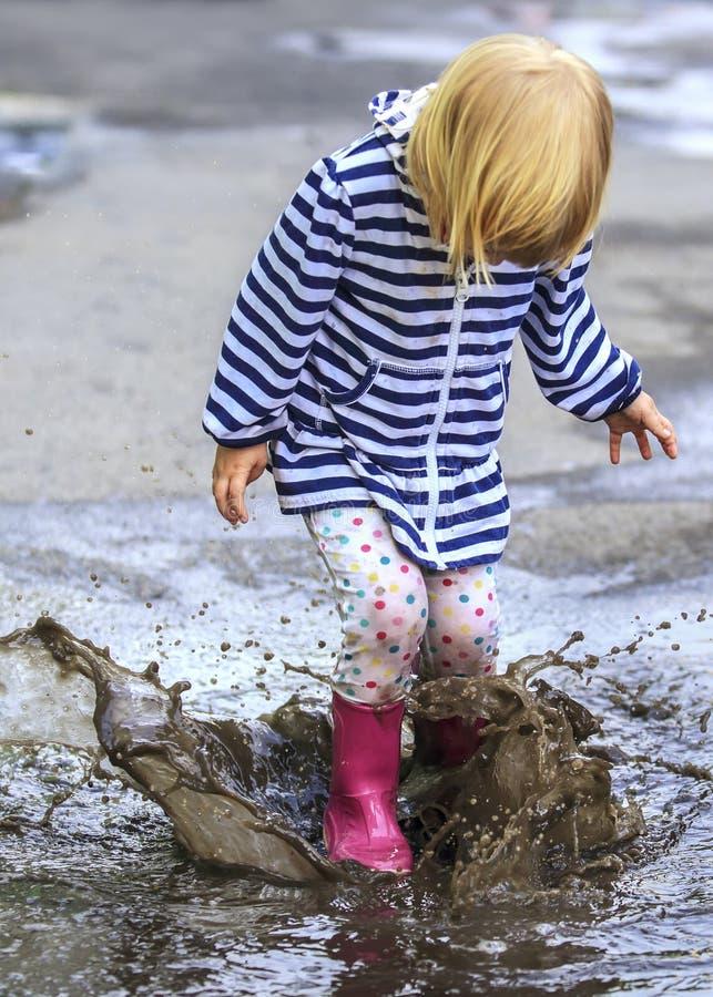 Saut extérieur d'enfant espiègle dans le magma dans la botte photo stock