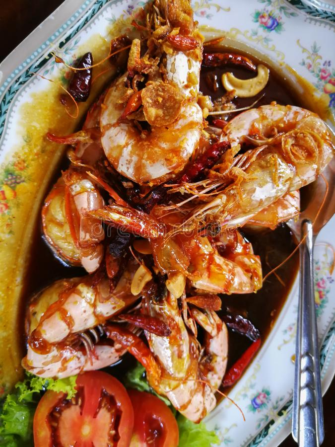 Saute shrimps with vegetables and tomato on plate in the restaurant. stock image