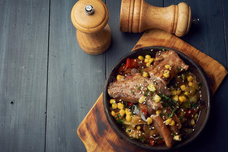 Sauteed свиные отбивние с caramelized овощами и мозолью в лотке литого железа стоковое фото