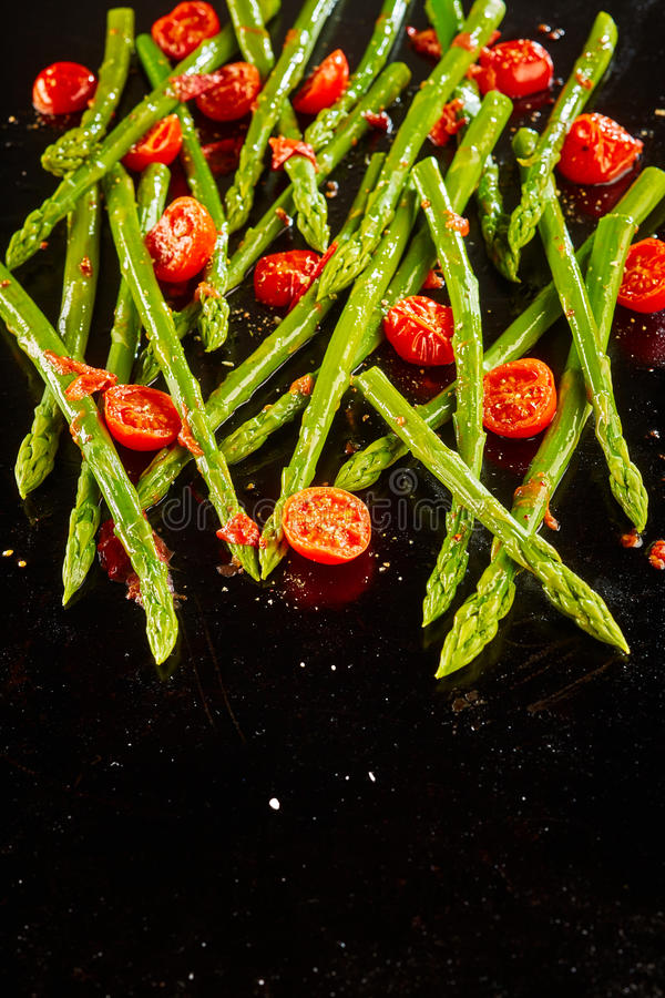 Sauteed fresh green asparagus spears with tomatoes royalty free stock photos