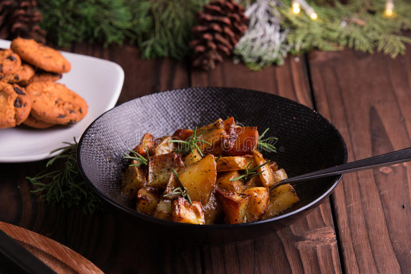 Sauteed sweet potato salad on black bowl on brown wooden background. Side dish for christmas, thanksgiving, and new year's eve din royalty free stock image