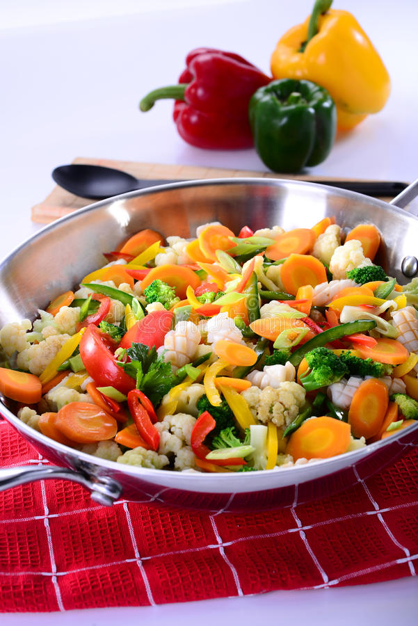 Sauteed vegetables with octopus, squid, carrots, chili, broccoli. On tablecloth deliciously stock photography