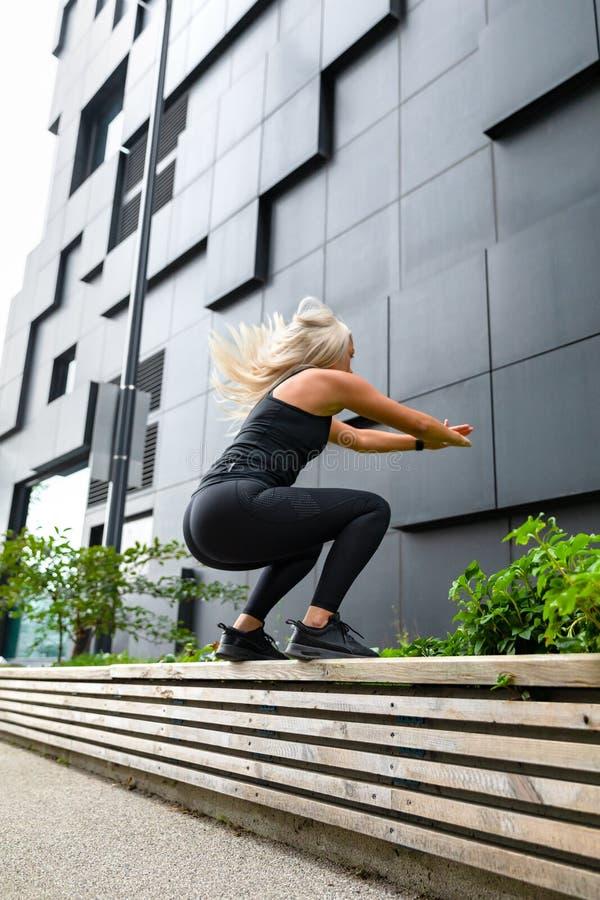 Sauter assidu de femme de forme physique extérieur dans le milieu urbain photographie stock libre de droits