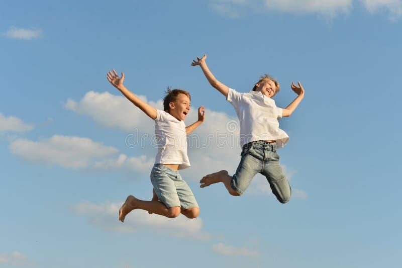Sauter de deux garçons images libres de droits