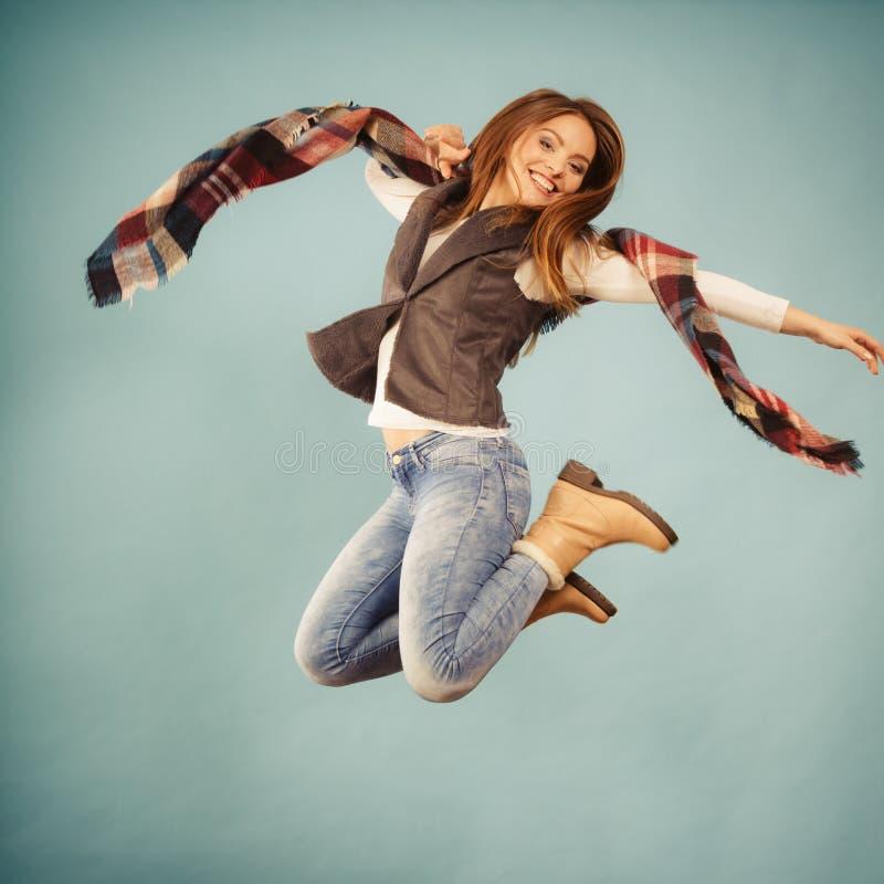 Sauter de fille d'automne de mode de femme, volant en air sur le bleu photographie stock