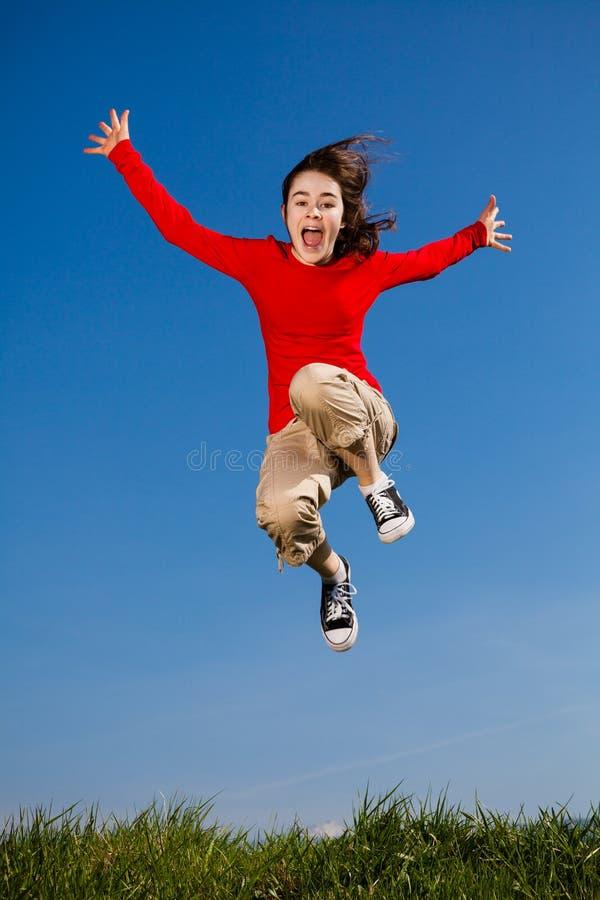 Sauter de fille, fonctionnant contre le ciel bleu photos libres de droits