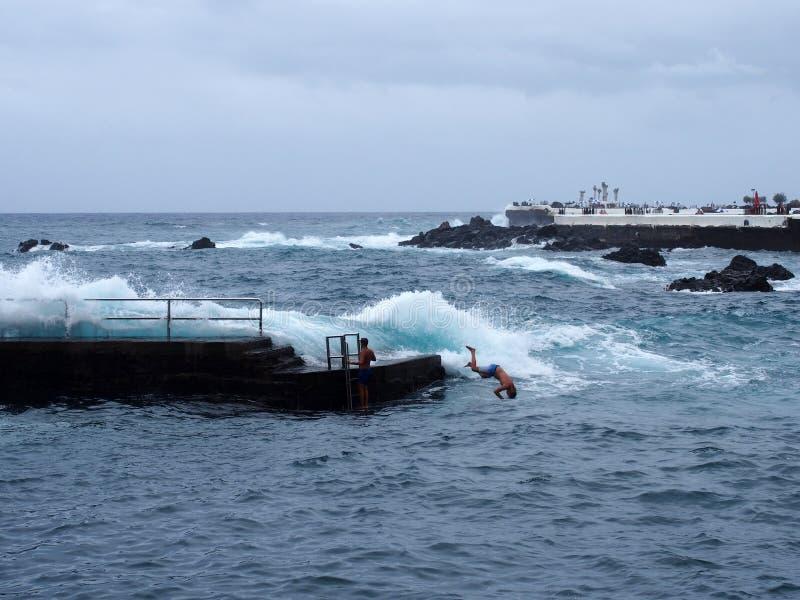 Sauter de jeune homme d'un pilier concret dans la mer avec des vagues de haute et du ressac en puerto de la cruz Ténérife photos stock