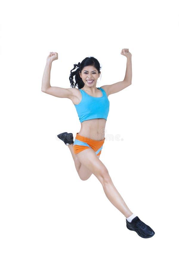 Sauter enthousiaste de femme de forme physique photographie stock libre de droits