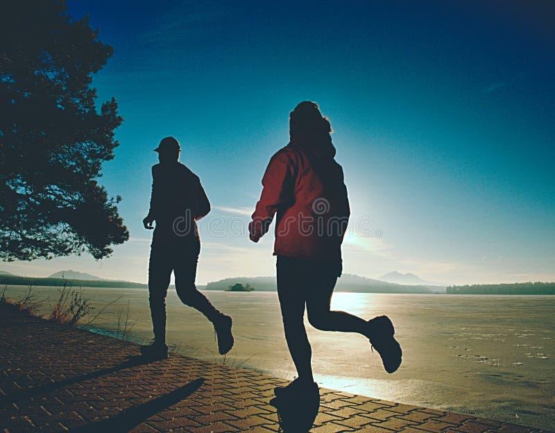 Sauter fou de couples de sports sur le chemin de parc autour du lac congelé images stock