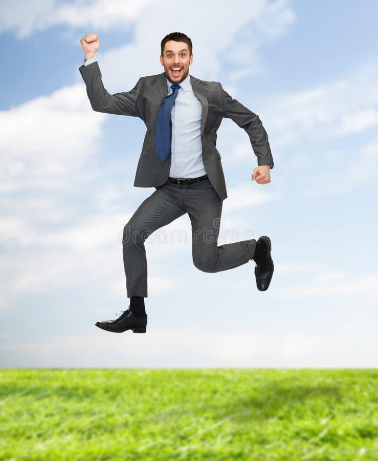 Sauter heureux de sourire d'homme d'affaires image stock