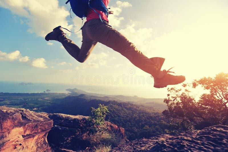 Sauter par-dessus le précipice entre deux montagnes rocheuses au coucher du soleil images libres de droits