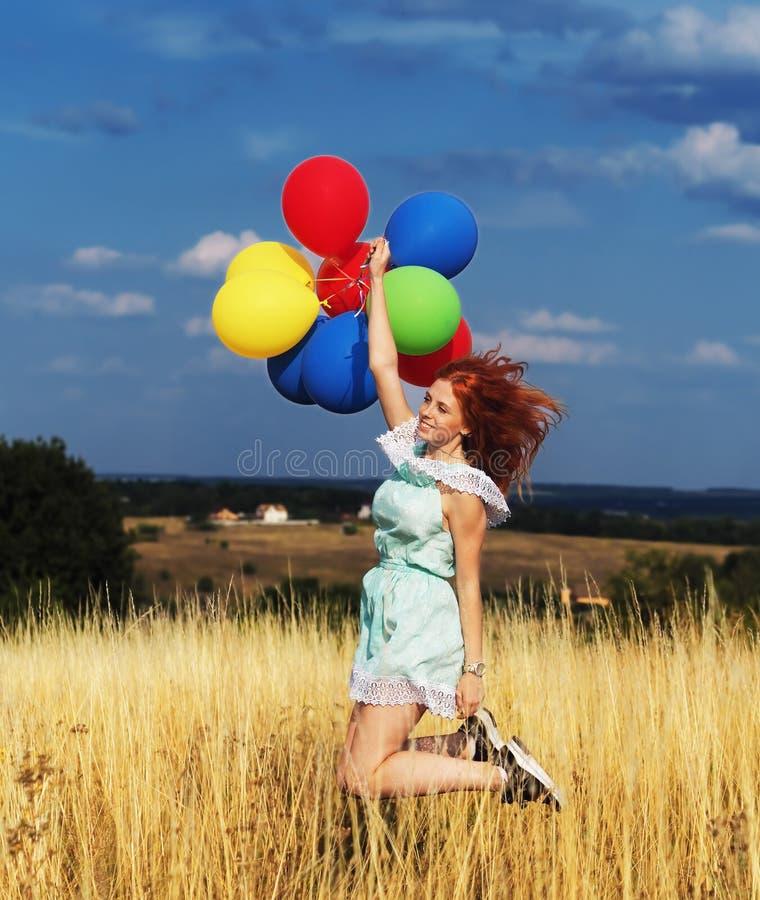 Sauter roux de fille avec des ballons aux ?pillets jaunes et au ciel bleu photos stock