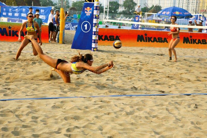 Sauvegarde de joueuse de femme dans le match de volley de plage photographie stock libre de droits