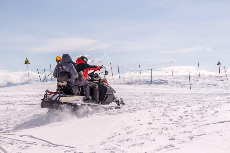 Sauveteurs sur des motoneiges dans les montagnes images libres de droits