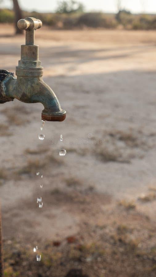 Sauvez chaque goutte de l'eau, s'égouttant le vieux robinet images libres de droits
