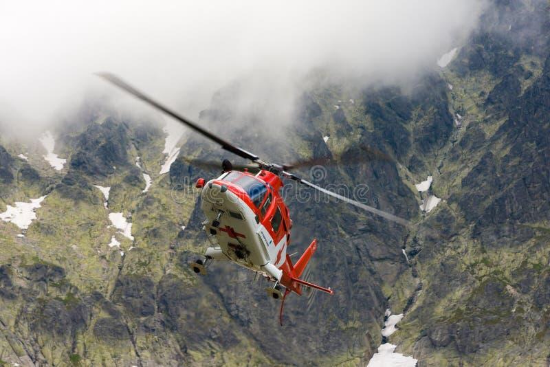 Sauvez l'hélicoptère décollant en tétra montagnes nuageuses dans slovaque images libres de droits