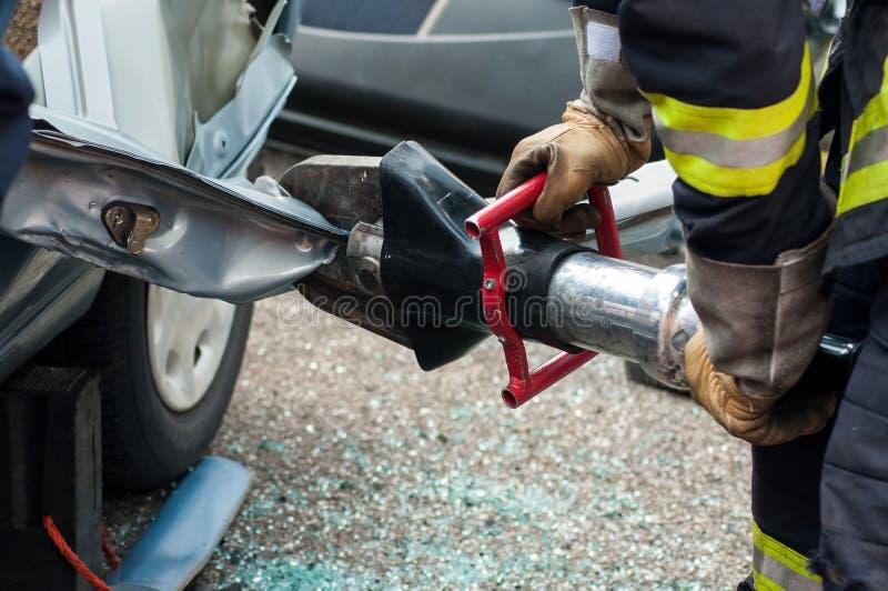 sauvez l'homme avec la machine pneumatique sur la voiture écrasée images libres de droits
