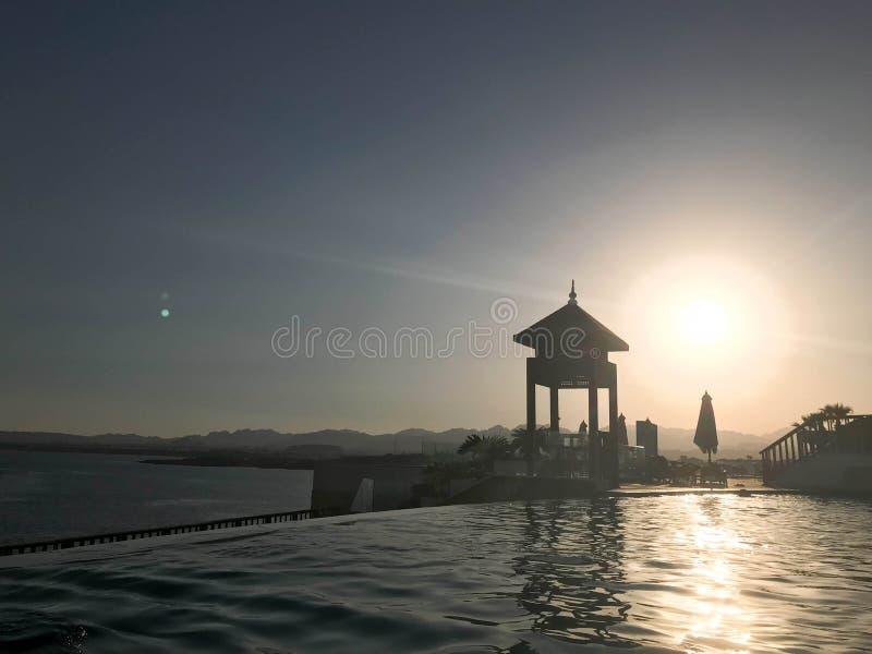 Sauvez la cabine, dominez, sauvez le courrier au bord de l'eau d'une piscine luxueuse d'infini fusionnant avec l'horizon contre l photographie stock libre de droits