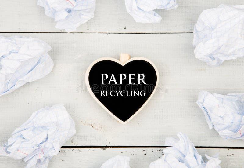 Sauvez le concept de planète - papier chiffonné autour d'un tableau noir dans la forme du coeur et de la réutilisation de papier  image libre de droits