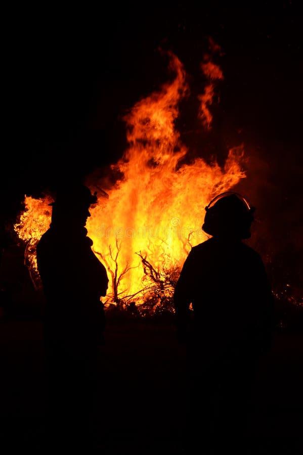 Sauvez les sapeurs-pompiers regardant dans l'oeil du feu de brousse  image stock