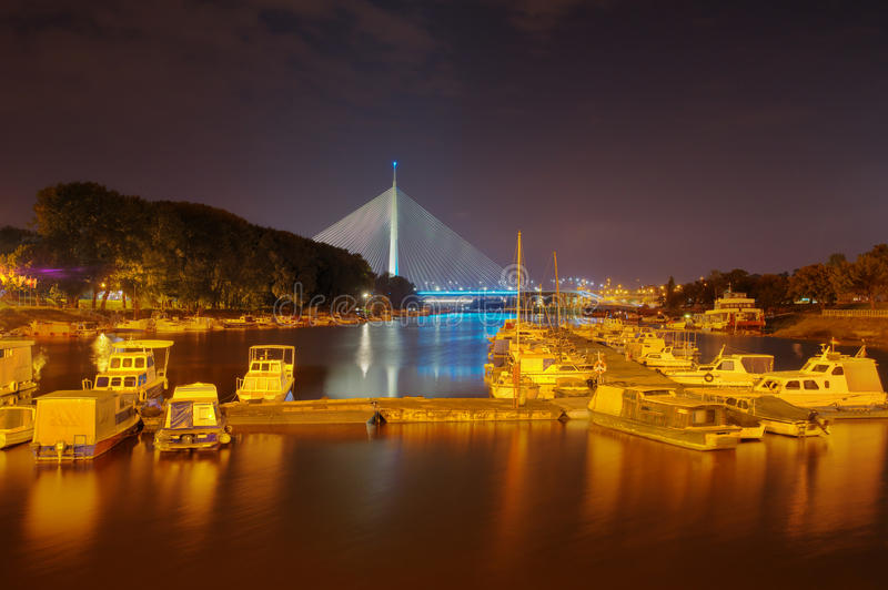 Sava river, marina and Ada bridge in Belgrade, Serbia - night picture. Yachts, reflections and lights create a romantic mood stock image