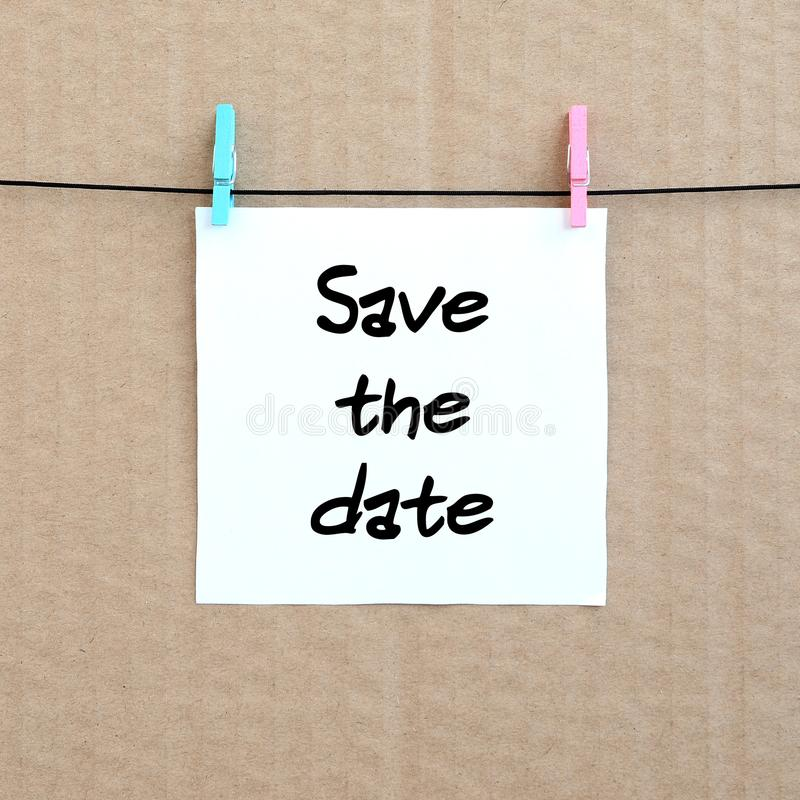 Save the date. Note is written on a white sticker that hangs wit royalty free stock image