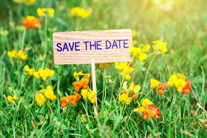 Save the date signboard. Save the date on small wooden signboard in the green grass with flowers and sun ray royalty free stock photo