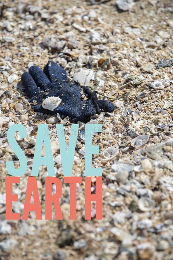 A deep blue winter yarn glove found trashed on the beach. Save Earth please!. Save Earth awareness on the Earth day. A deep blue winter yarn glove found trashed stock photography