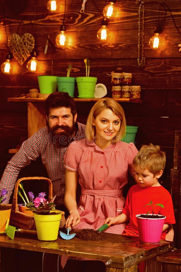 Save Earth concept. Little boy with family transplanting flower in new pot to save Earth. Child with mother and father. Transplanting houseplant in dirt to save royalty free stock photos