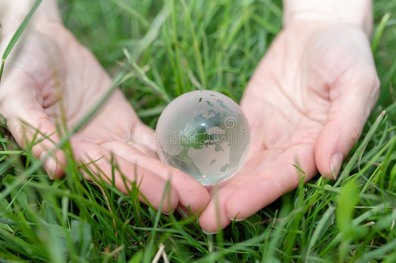 Save Earth consept. Environment concept. Glass ball in female hands. green grass background stock image
